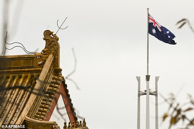 Australia's parliamentary flag pole in Canberra seen behind the roof of the Chinese Embassy on Monday. The new $1.35 billion boost will help Australia defend itself against cyber attack