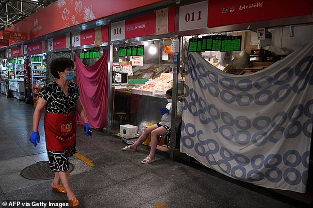 A vendor is seen walking past closed stalls at a food market in Beijing on June 22. Beijing Authorities have clamped down on food production and distribution amid a new coronavirus cluster linked to the Xinfadi wholesale market. A total of 318 native infections have been found