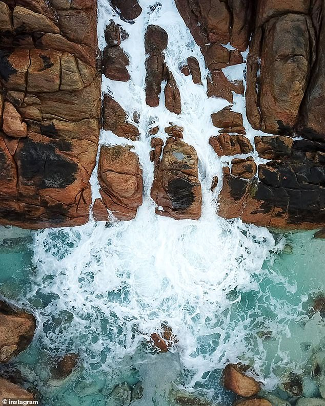 He had been exploring the popular selfie spot with five friends when the large swell knocked him off the rocks about 5.10pm