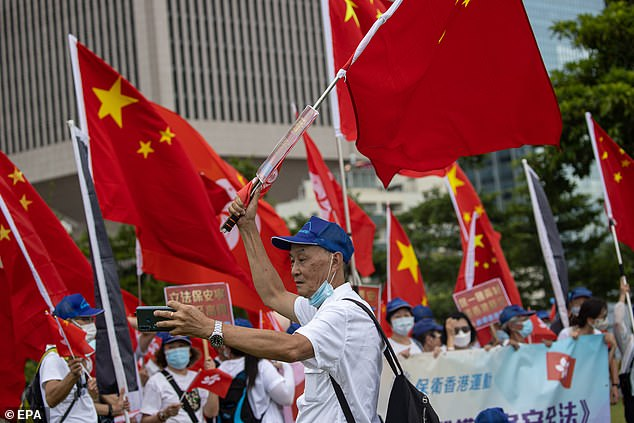 A pro-China supporter takes a selfie at a rally in Hong Kong today as news filtered out that the new security law had been passed