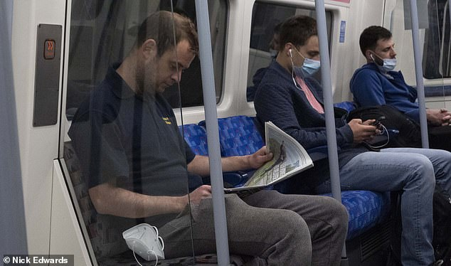 A man reads a newspaper while not wearing his mask during his commute on the Tube today