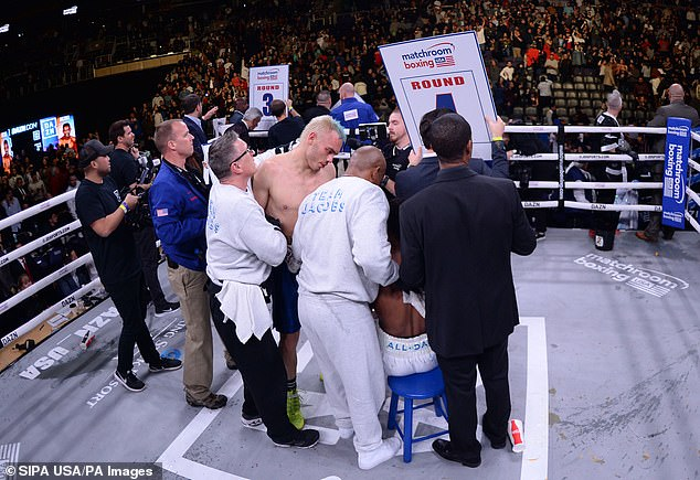 Julio Cesar Chavez Jr (standing, blonde and blue hair) and Daniel Jacobs (sat, obscured, in white trunks) are protected as fans pelt the ring with drinks and litter after the former quit