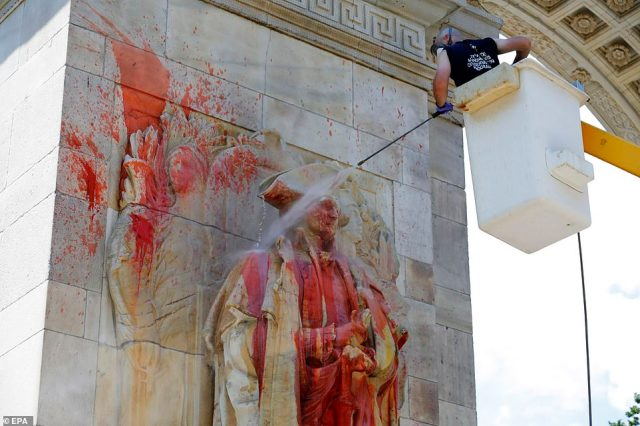 Clean-up: A member of the New York City Monuments and Conservation department power-washes the statue of Washington yesterday after it was vandalized