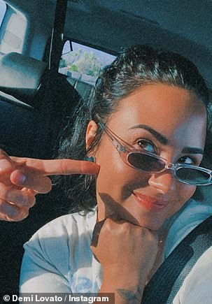 Wearing a white T-shirt and narrow sunglasses, Demi kept snapping selfies as she and Max smooched