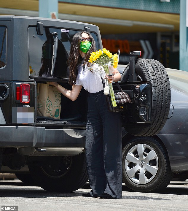 Trendy: She put her groceries into her Jeep while clutching the bouquet of sunflowers. She showed off her designer taste with a Bottega Veneta padded shoulder bag, worth AUD$3,850