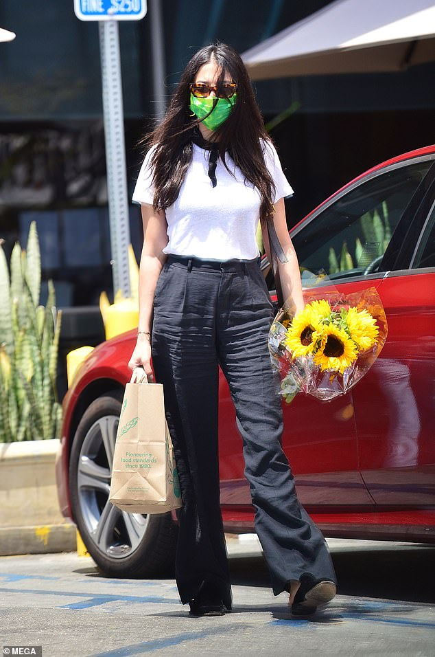 Chic:Jessica Gomes (pictured) stood out from the crowd as she covered her face in a neon green mask while stopping by the Wholefoods in Los Angeles on Monday