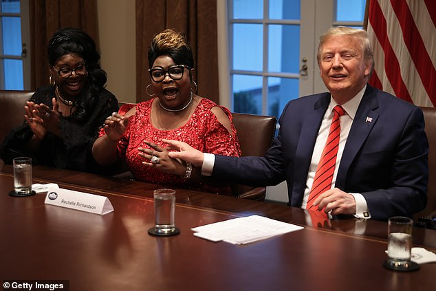 President Donald Trump (R) listens as Lynette 'Diamond' Hardaway (L) and Rochelle 'Silk' Richardson praise him during a news conference and meeting with African American supporters in the Cabinet Room at the White House February 27, 2020