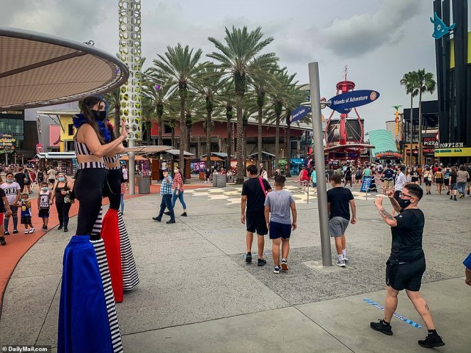 Performers are seen on stilts and wearing face coverings at Islands of Adventure