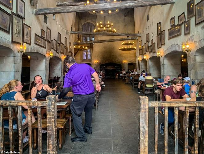 People are seen socially distanced and wearing face masks at The Wizarding World of Harry Potter - Diagon Alley attraction at Universal Studios