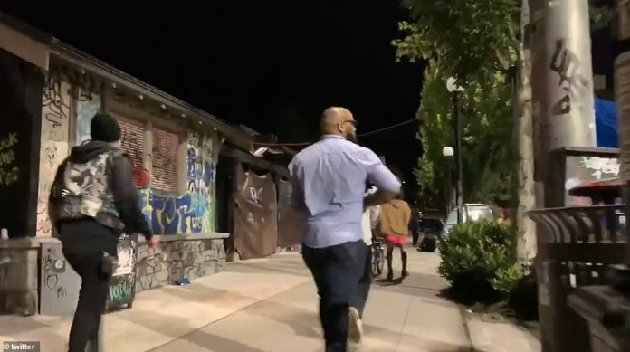 A second video shows people running through barricaded streets past tents