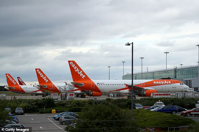 EasyJet revealed up to 4,500 staff will lose their jobs, including 1,900 UK employees (pictured, EasyJet planes at Stansted Airport today)