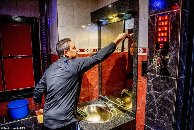 Pictured: A man cleans the windows of a bathroom in one of buildings that houses the rooms the sex workers in Amsterdam's red light district rent