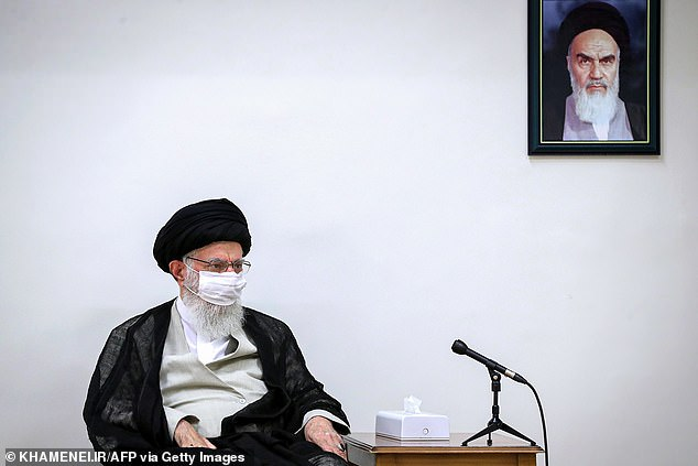Pictured: Iran's Supreme Leader Ayatollah Ali Khamenei clad in a face mask as a protective measure due to the COVID-19 coronavirus pandemic, while seated beneath a picture of his predecessor Ayatollah Ruhollah Khomeini, during a meeting in the capital Tehran, June 30