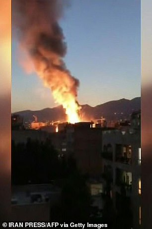 Pictured: Fire and smoke rise from the building, shown in footage recorded from a near-by building of the explosion in Tehran on June 30, 2020