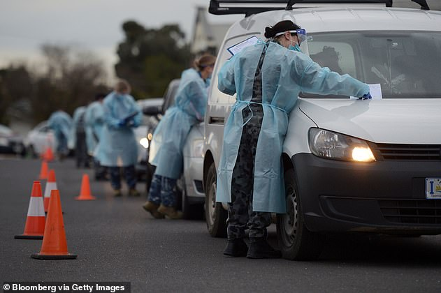 Health authorities have been scrambling to contain the outbreak with a 'testing blitz' (pictured, members of the ADF carry out temperature checks on motorists on Tuesday)