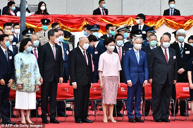 Hong Kong's Chief Executive Carrie Lam (central) stands with former chief executives as they attend a flag-raising ceremony to mark China's National Day celebrations early