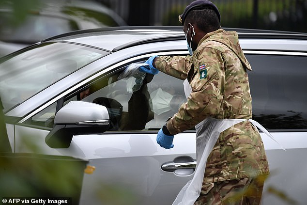 Speaking to the country ahead of the UK's 100th day in lockdown, Mr Johnson said the failures in dealing with the pandemic had made it feel like being in a 'recurring bad dream'. Pictured: A soldier passes a self-test to a member of the public in Leicester