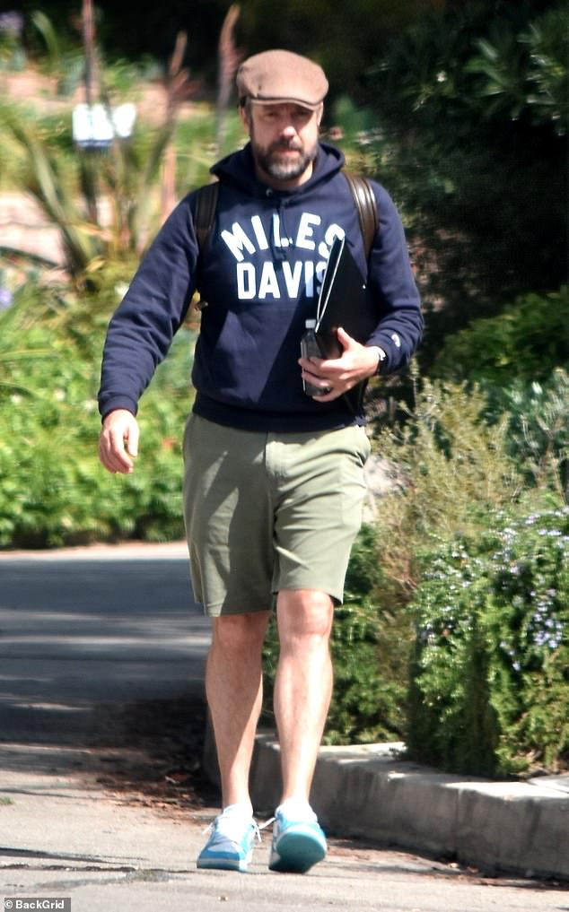 Casual: Jason, 44, was dressed in a navy hoodie and khaki green knee-length shorts along with turquoise trainers. The bearded star added a flat cap and a backpack to his ensemble.