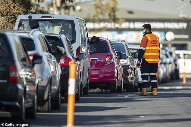 Staff direct traffic in massive queues waiting to get into a pop-up COVID-19 test site in Fawkner on Wednesday