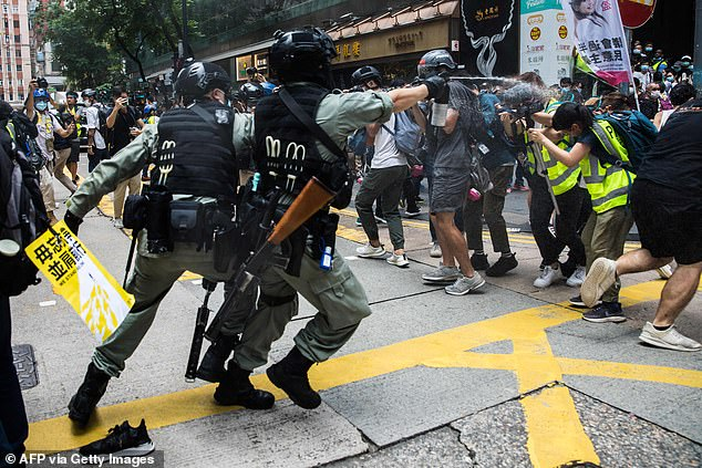 Riot police deploy pepper spray towards journalists as protesters gathered for a rally against the new national security law in Hong Kong