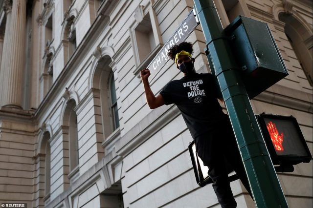 A demonstrator climbs a traffic lamp wearing a shirt that reads 'defund the police' ahead of a city hall vote that stripped $1billion in funding from the NYPD