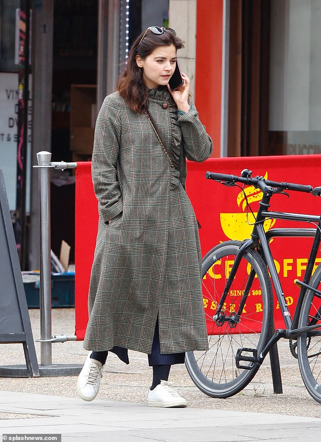 Typically chic: The Victoria star, 34, looked effortlessly stylish as she wrapped up in a check-print maxi coat during her casual appearance