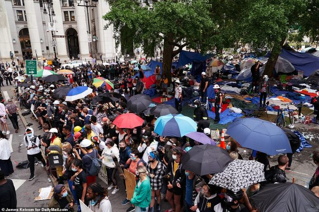 Hundreds of protesters have occupied the park and are refusing to disperse. On Wednesday morning, they huddled beneath umbrellas and chanted 'hold your ground' as the cops tried to move them back into the park