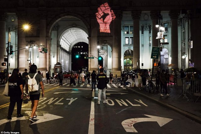The Black Lives Matter fist symbol is projected onto the walls of the city as protesters gathered another night