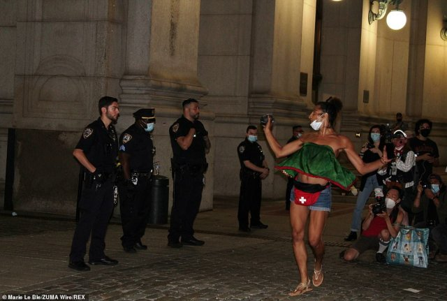 Moments earlier the protester was seen dancing provocatively in front of a line of cops