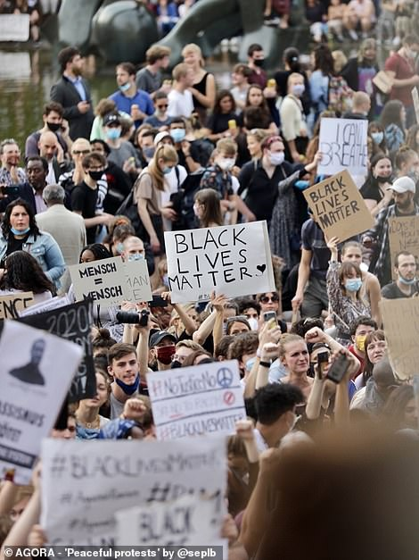 Pictured: People in Germany take part in a Black Lives Matter protest. One person holds a sign that reads 'Mensch = Mensch' which translates to 'Human = Human'