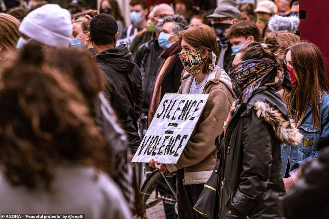 Pictured: A woman holds a sign that reads 'silence = violence' at a Black Lives Matter protest in the UK
