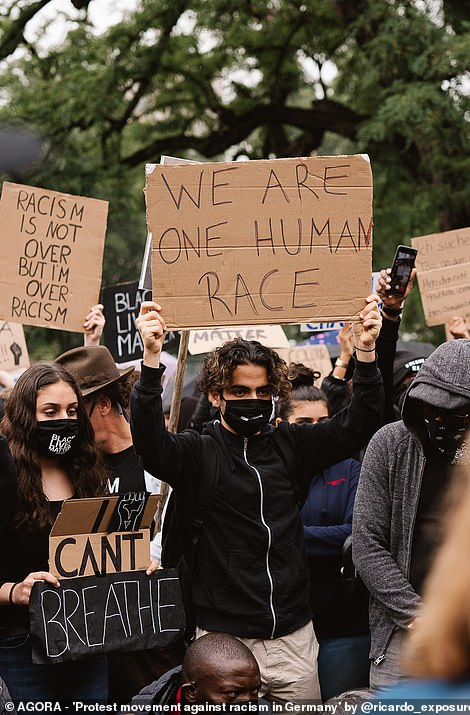 Protestors in Germany join the Black Lives Matter protests, holding signs that read 'We are one human race' and 'Racism is not over but I'm over racism'
