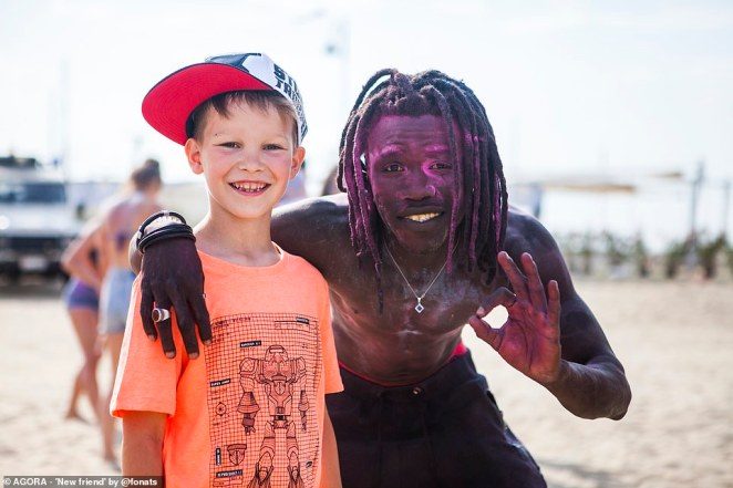 Pictured: A black man covered in pink paint puts his arm around a younger smiling white white boy at the beach