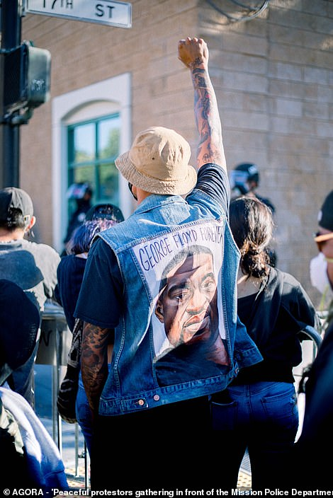 Peaceful protesters gather in front of the Mission Police Department. One man wears a jacket with a picture of George Floyd's face on the back