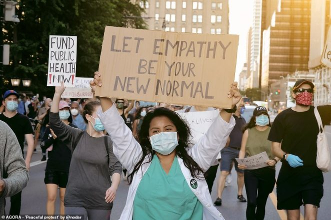 Pictured: A nurse joins protesters in marching down the street with a sign that reads 'let empathy be your new normal'
