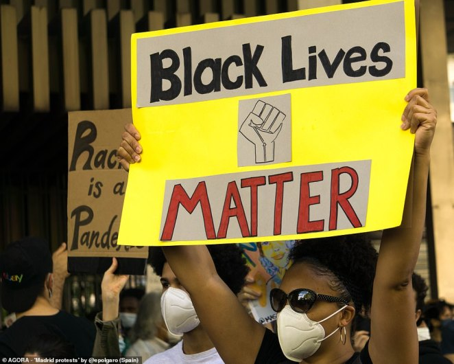 Pictured: A woman wearing a mask holds a Black Lives Matter sign at protests in Madrid, Spain