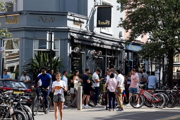 Wagerers are pictured drinking by Wandsworth Common in London at the Althorpe pub serving takeout beers