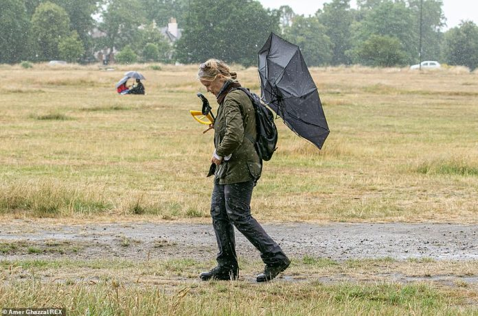 A person walks with an overturned umbrella during rain showers on Wimbledon Common, London, today