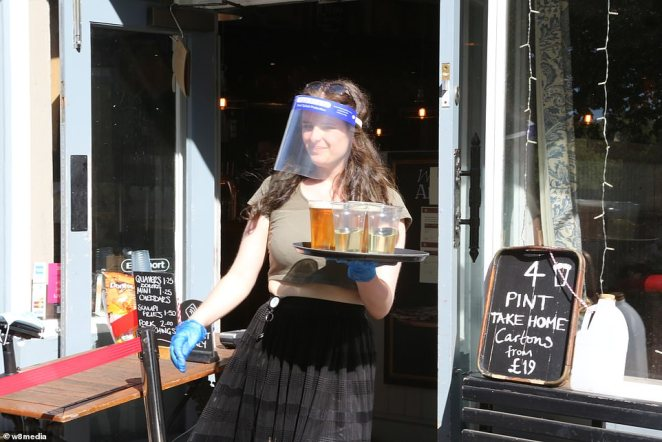 A member of staff at The Althorp by Wandsworth Common wears PPE while serving customers