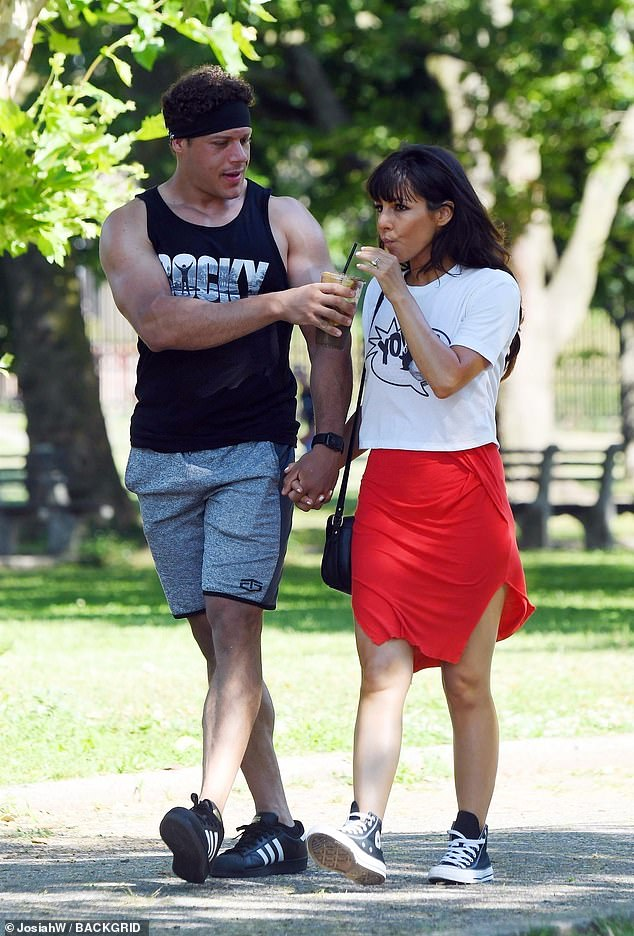 Sharing is caring: Meanwhile, Jason showcased his muscular physique in a black 'Rocky' vest top, grey shorts and black trainers, adding a black sweat band to his head