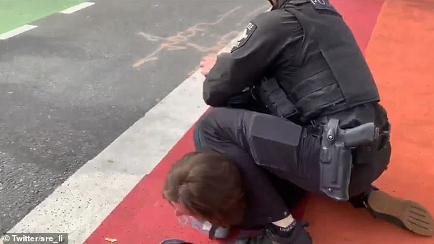 The officer presses his knee against the protester's neck as he is arresting him. The protester is heard asking the officer to remove his knee from his neck