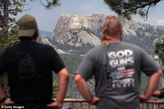 Health experts say the event could lead to a spike in cases, and put not only attendees but also workers at risk. Pictured:Visitors look at Mount Rushmore National Monument, July 2