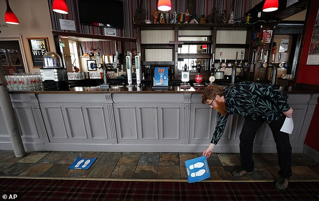 Pubs and bars are implementing measures to encourage social distancing and safe hygiene to reduce the risk of the coronavirus spreading as they reopen on Saturday. Above,  Owner Are Kjetil Kolltveit from Norway places markers for social distancing on the front of the bar at the Chandos Arms pub in London