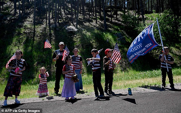 Supporters of US President Donald Trump wave flags on a road in Keystone, South Dakota, on July 3