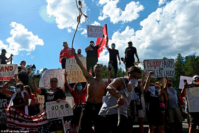 Crowds gathered with signs and placards reading: 'this is stolen land' and'Protect SoDak's First People' ahead of Trump's arrival