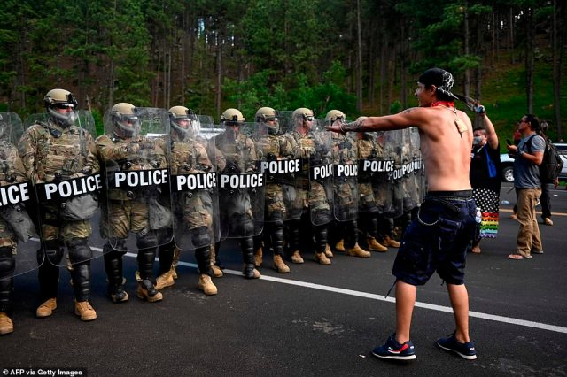 About 15 people were arrested after ignoring police orders to clear the area. Pictured: A protesters approaches a line of police in riot gear during Friday's standoff