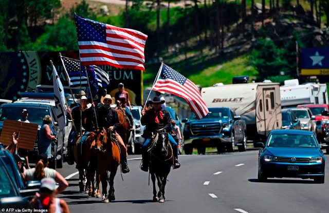 Trump supporters on horseback go through Keystone, South Dakota ahead of his planned appearance Friday night at Mount Rushmore