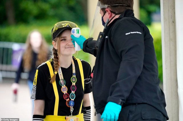 A member of the public has her temperature checked at the entrance to Alton Towers this morning by a member of staff wearing gloves, a mask and a face shield as the popular theme park reopens today
