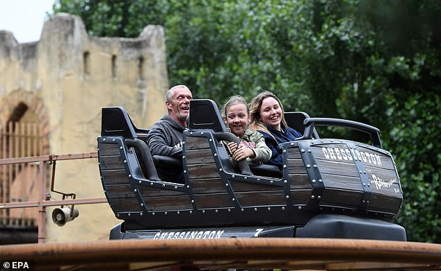 Three people smile as they ride a rollercoaster at World of Adventures in Chessington, Surrey, on Saturday afternoon