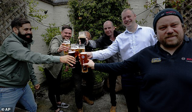 Men raise their glasses for a cheers as they enjoy their first beers as the Chandos Arms pub reopened in north west London on Saturday afternoon